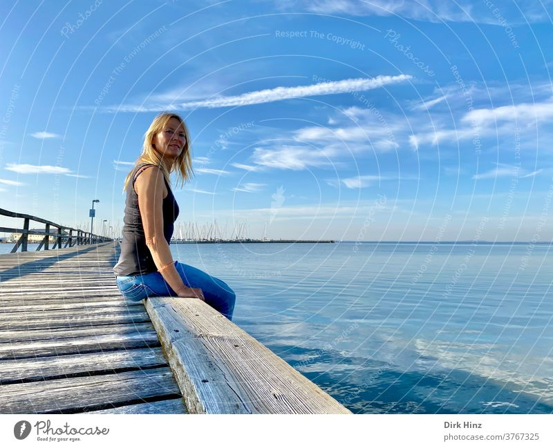 Blonde woman sitting on a pier on the Baltic Sea coast Woman 45 - 60 years already portrait Staring Looking Human being Adults Feminine Looking into the camera