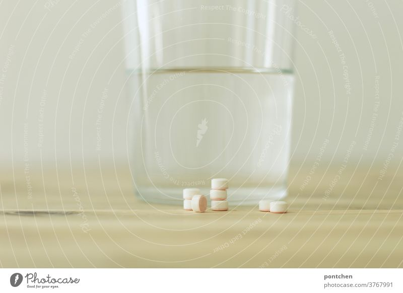 Several tablets piled up are lying on a table in front of a drinking glass filled with water. Sickness, medication. Addiction to pills. medicine Tumbler Illness