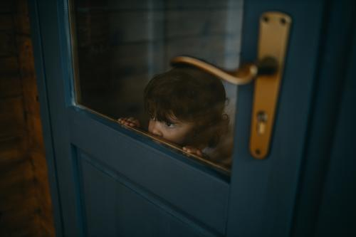 Child looking through door childhood Looking Door Glass Caucasian Christmas & Advent confinement Quarantine at home Home caucasian stay at home Colour photo