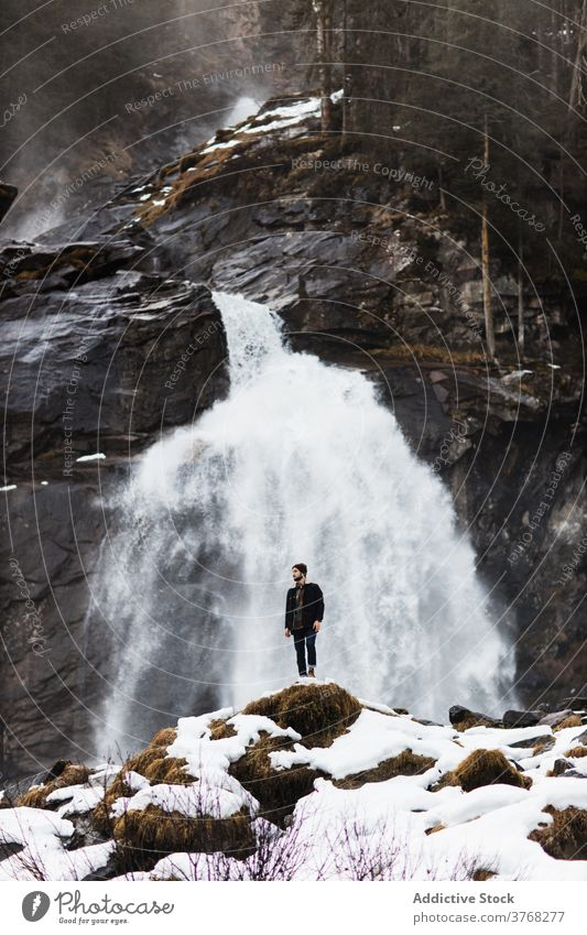 Traveling man near waterfall in mountains traveler winter highland hiker nature landscape stream male germany austria snow adventure hill trip journey tourism