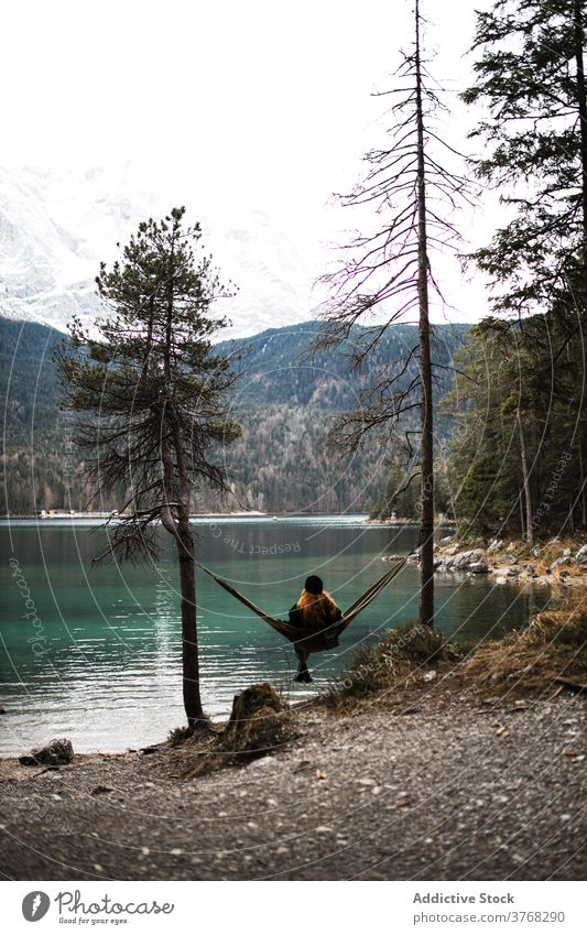Woman relaxing in hammock near lake woman mountain admire scenery pond highland autumn female germany austria majestic nature traveler serene tourism peaceful