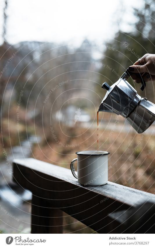 Traveler pouring hot coffee into mug in autumn nature travel enamel hot drink break rest together countryside beverage cup relax trip journey warm season