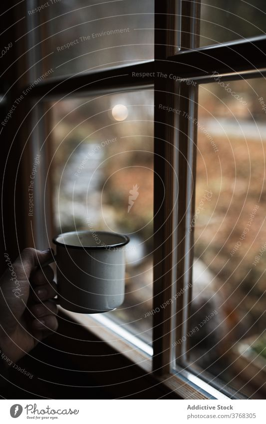 Anonymous person enjoying hot drink near window in cold autumn day mug countryside cup coffee cozy enamel beverage travel rest relax fall season warm calm tea