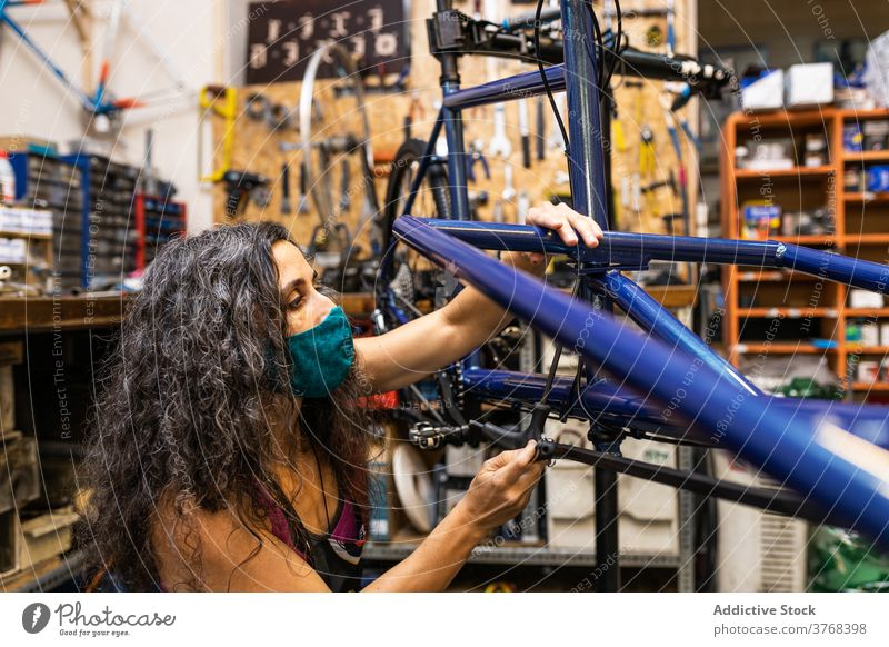 Woman fixing bike in workshop bicycle repair woman mechanic maintenance service install brake wire occupation female ethnic professional job busy skill
