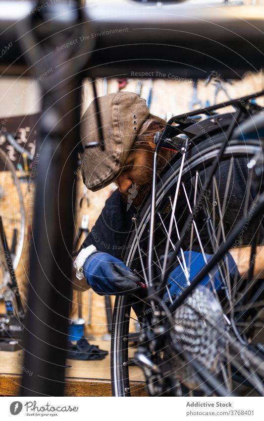 Repairman fixing bicycle wheel in workshop repair mechanic spoke maintenance bike occupation service male beard mature professional job repairman labor handyman