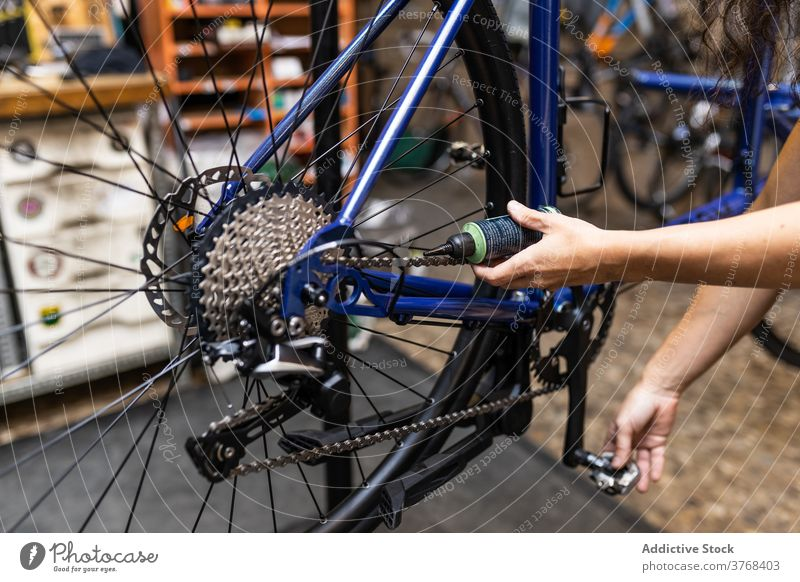 Technician oiling bike chain in workshop bicycle repair mechanic maintenance service fix occupation professional job workplace hand manual pedal vehicle