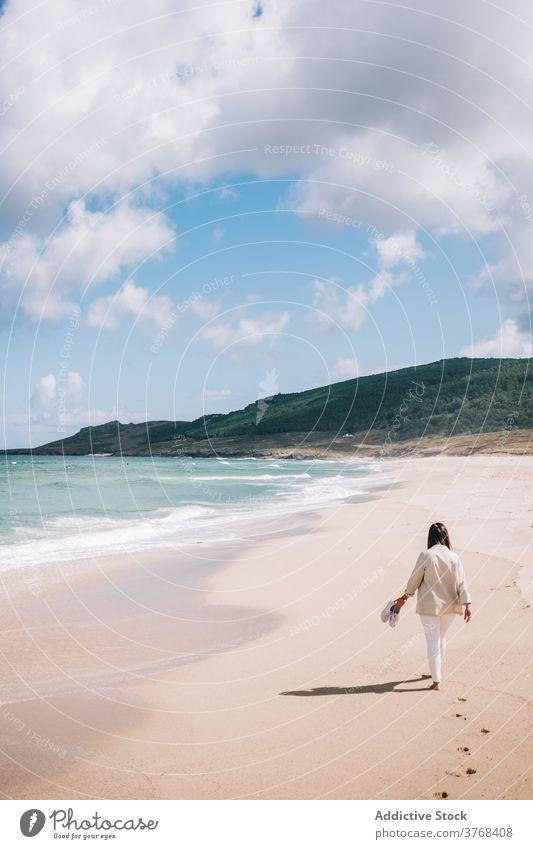 Woman walking admiring waving sea on beach woman wave sand fresh stormy alone seaside shore female travel tourism spain barefoot enjoy relax recreation breeze