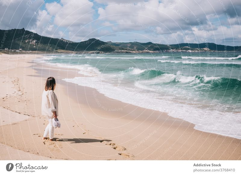 Woman admiring waving sea on beach woman wave sand fresh stormy alone seaside shore female travel tourism spain barefoot enjoy relax recreation breeze summer