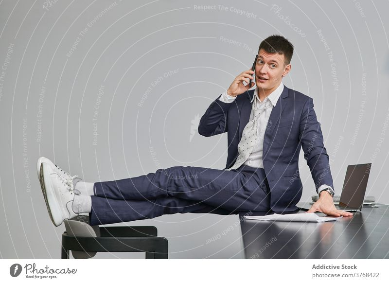Stylish businessman speaking on cellphone in office project smartphone discuss sit table entrepreneur style male workplace chair conversation occupation device