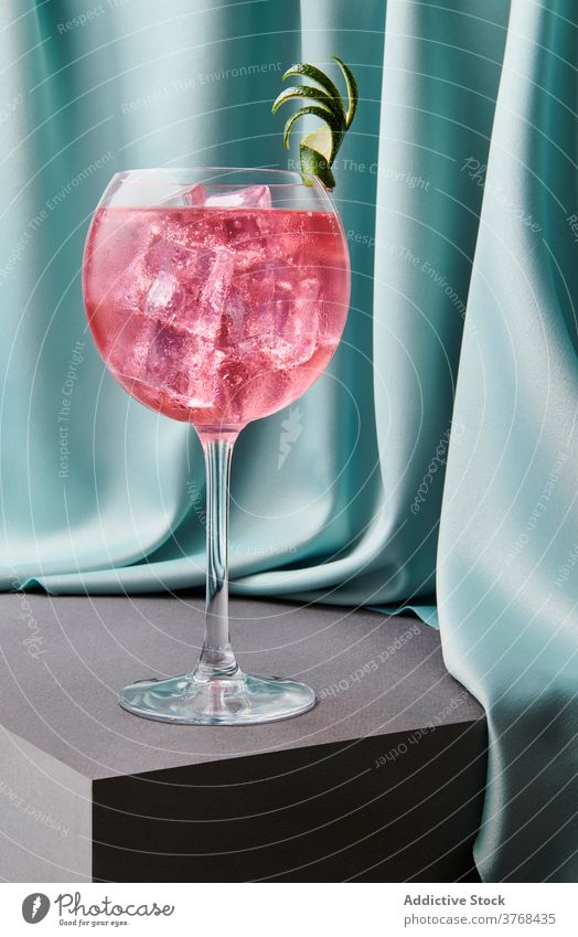 Glass of Cosmopolitan refreshing cocktail on table cosmopolitan lime alcohol glass refreshment beverage drink peel ice cube crystal goblet red bar cool liquid