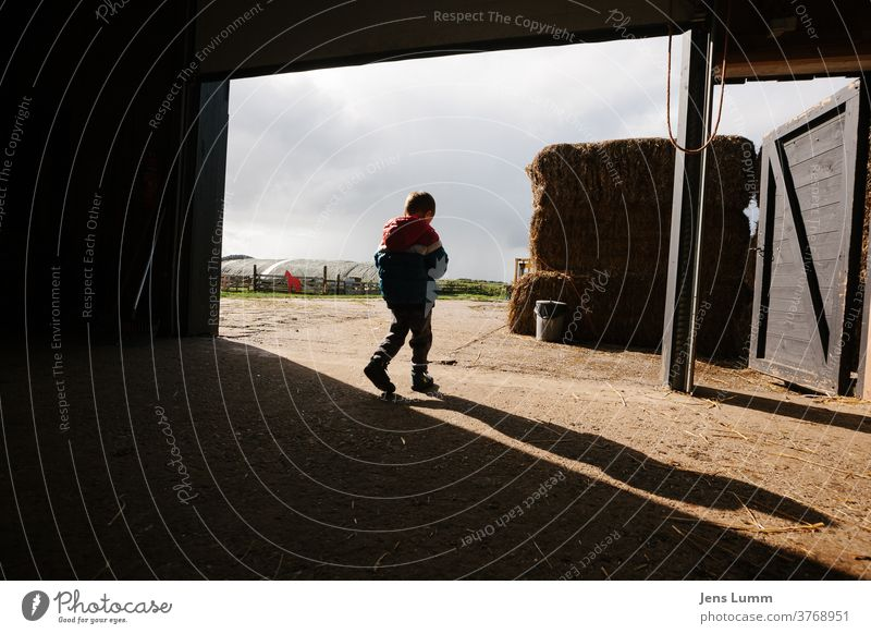 Boy leaves barn on farm Boy (child) Child Farm Shadow Hay Hay bale Barn chill Summer vacation cloudy sky Netherlands Sunlight lost in thought brood undecided