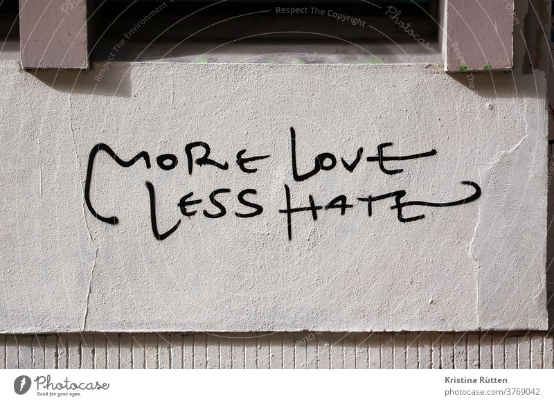 more love less hate written on a house wall Love no Hatred Graffiti street art slogan motto statement Remark saying next love togetherness Tolerant