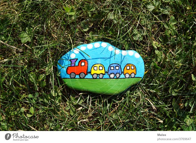 A painted hiking stone is left on the walking path for passersby to see park adventure background border cartoon child clearing climb color creature design
