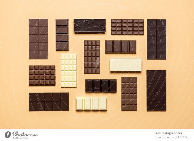 Chocolate bar assortment isolated on yellow background. Assorted chocolate creative layout assorted baking beige bitter chocolate bar christmas collection