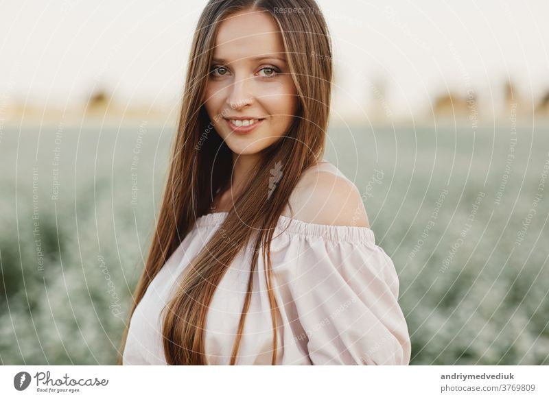 Beautiful woman enjoying field, happy young lady and spring green nature, harmony concept. portrait of a beautiful girl in a field of flowers. selective focus