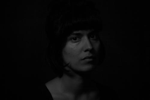 Black and white portrait of an indian girl on black background dramatic tension indiana beautiful sensual dark sadness illuminated obscure black and white
