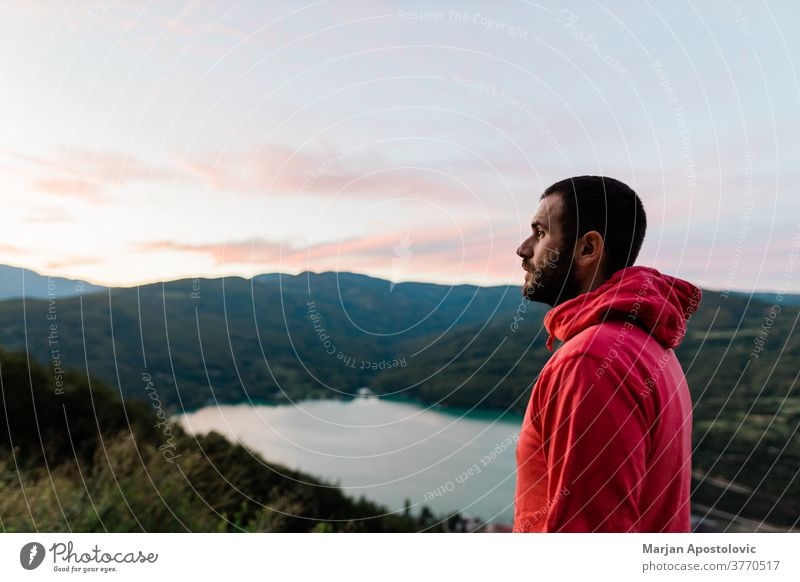 Young man enjoying the view of the lake in sunset adventure adventurous alone casual contemplation dawn destination dusk evening explore explorer free freedom