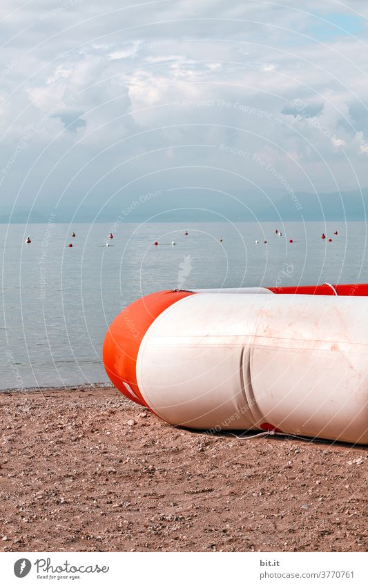 large life ring, lies under cloudy sky, on the lake shore, on the sandy beach. Lake Rescue Life belt Savior Rescue equipment Tire Swimming & Bathing Water wings
