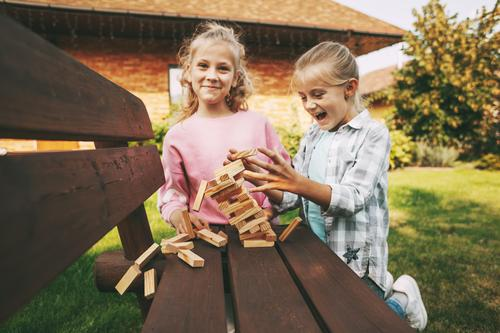 Two girls are having fun and playing a wooden board game outdoors near their home. children leisure development tree sister three happy cube useful smart family