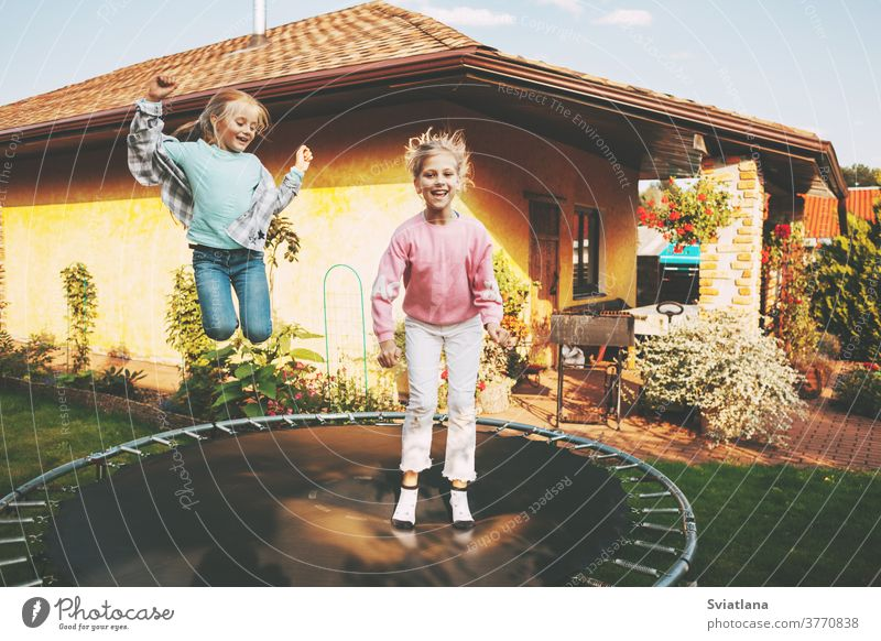 Happy two blonde girls are jumping on a trampoline in the garden near their house. Leisure and games children together happy childhood caucasian summer fun