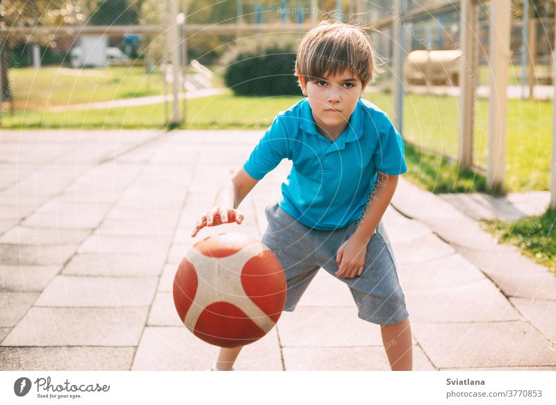 Focused cute boy athlete leads the ball in a game of basketball. A boy plays basketball after school. Sports, healthy lifestyle dribbling sport player male