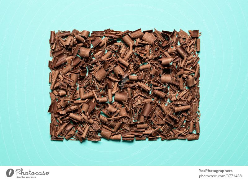 Chocolate pieces pile isolated on blue background. Chopped chocolate top view baking bitter brown chocolate shavings chopped christmas chunks confectionery