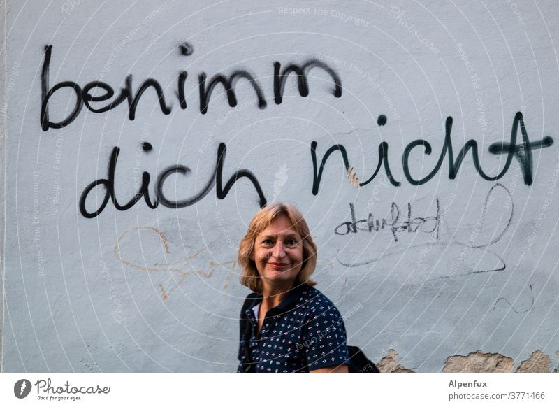 Motto of the week: Don't behave! Wall (building) Woman Face of a woman Human being Adults Colour photo Wall (barrier) Feminine Exterior shot portrait Day
