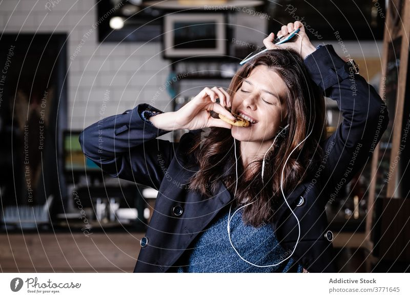 Delighted woman listening to music in cafe carefree enjoy eat cookie smartphone earphones female delicious eyes closed food weekend gadget happy pleasure