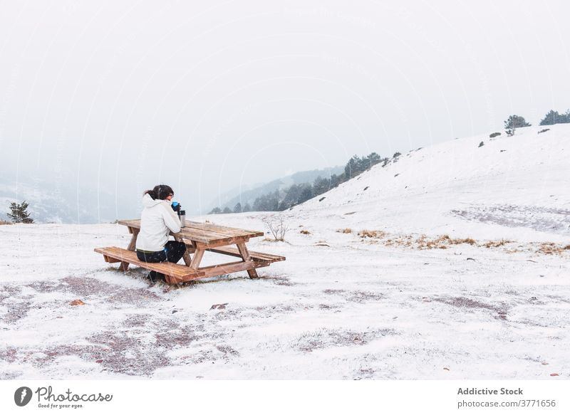 Unrecognizable tourist sitting on bench in mountains in winter traveler hot tea enjoy snow landscape tourism amazing pyrenees catalonia spain thermos table