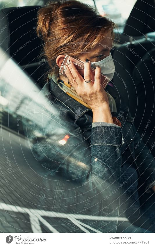 Woman talking on phone using smartphone sitting in a car wearing the face mask to avoid virus infection caucasian covid-19 lifestyle outbreak pandemic woman