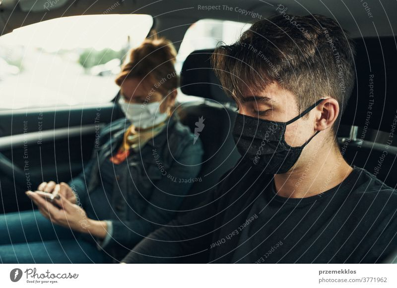 Man and woman sitting in a car using smartphones wearing the face masks to avoid virus infection caucasian covid-19 lifestyle outbreak outdoors pandemic