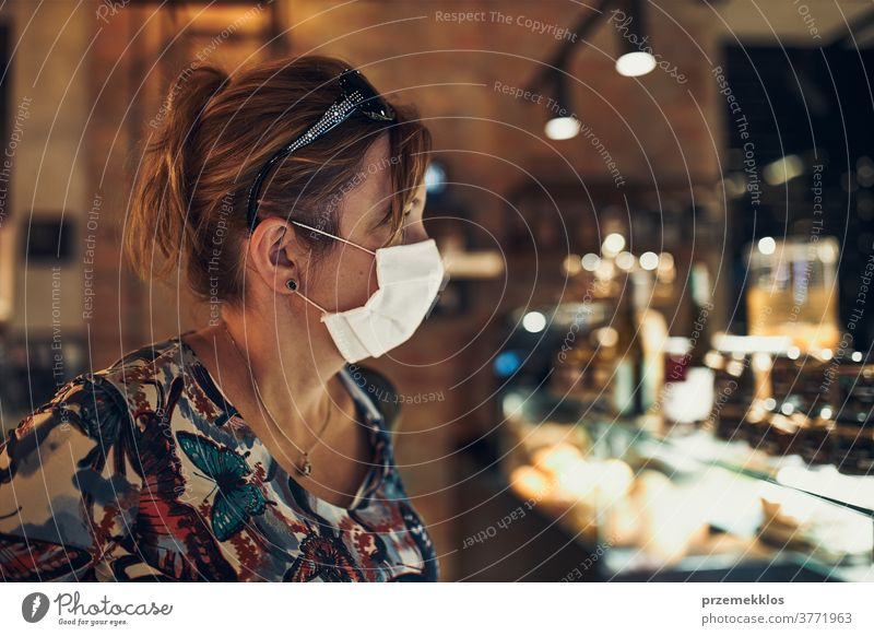 Young woman shopping in grocery store, wearing the face mask to avoid virus infection caucasian conversation covid-19 lifestyle outbreak outdoors pandemic