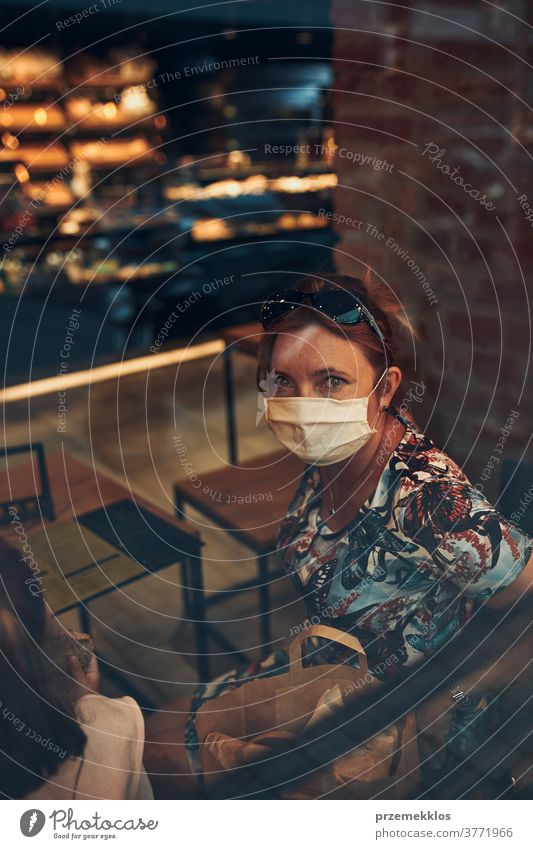 Young woman sitting in coffee shop at store front in the city center, wearing the face mask to avoid virus infection caucasian conversation covid-19 lifestyle