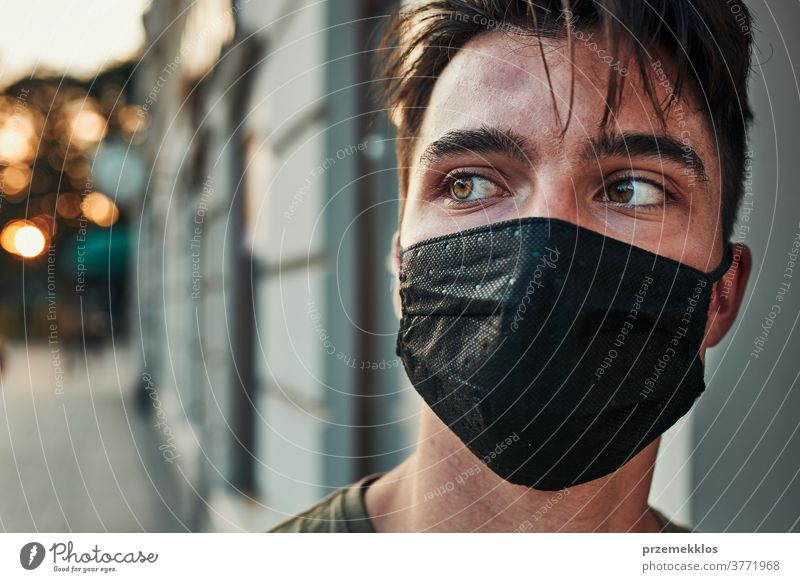Young man walking along a store front in the city center wearing the face mask to avoid virus infection caucasian conversation covid-19 lifestyle outbreak