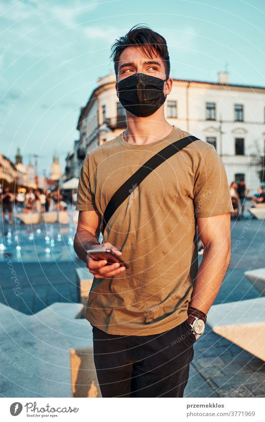 Young man standing in the city center wearing the face mask to avoid virus infection caucasian conversation covid-19 lifestyle outbreak outdoors pandemic
