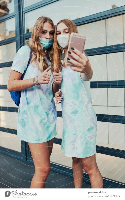 Young women girls taking selfie wearing face masks to avoid virus infection caucasian cellphone conversation covid-19 female lifestyle mobile outbreak outdoors