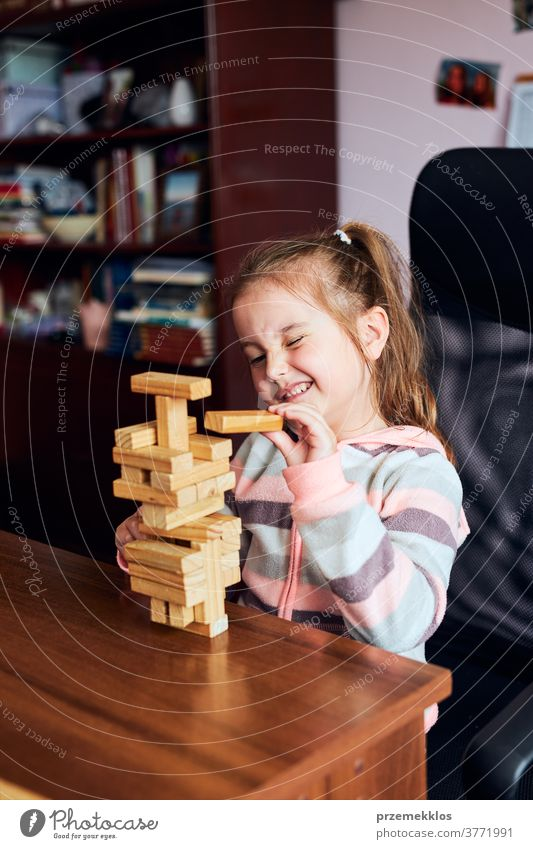 Little girl preschooler playing with wooden blocks toy building a house activity brick child childhood concept construction creativity education fun funny game