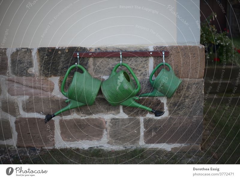 Three watering cans on church wall Watering can Suspended Cemetery Cast Day Green Colour photo Exterior shot Plastic Jug
