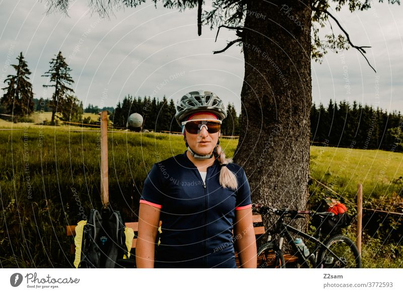Portrait of a female cyclist on a cycling tour in the countryside bike tour Cyclist Mountain bike Nature Landscape Tree Meadow Bavaria Helmet Sunglasses