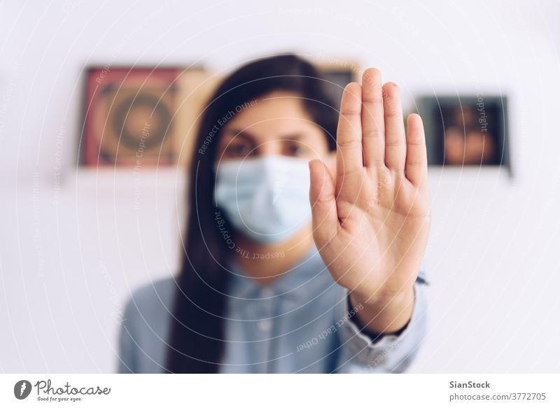 Coronavirus concept. Girl wearing a mask for protection say stop with her hands to coronavirus. Global call to stay home. covid quarantine 2019-ncov influencer