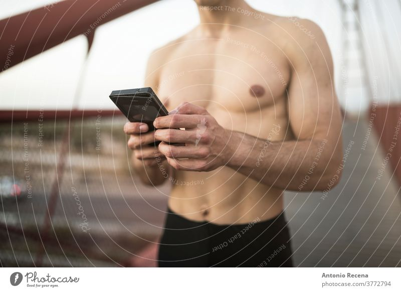 Shirtless runner training on red bridge and looking phone statistics man strong fit fitness footbridge footpath men male young adult one person torso muscular