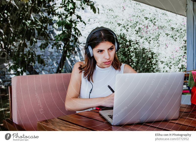 young latin woman sitting alone home office working on a laptop and listening to music on earphones, Mexican girl in Mexico working at home wireless browsing