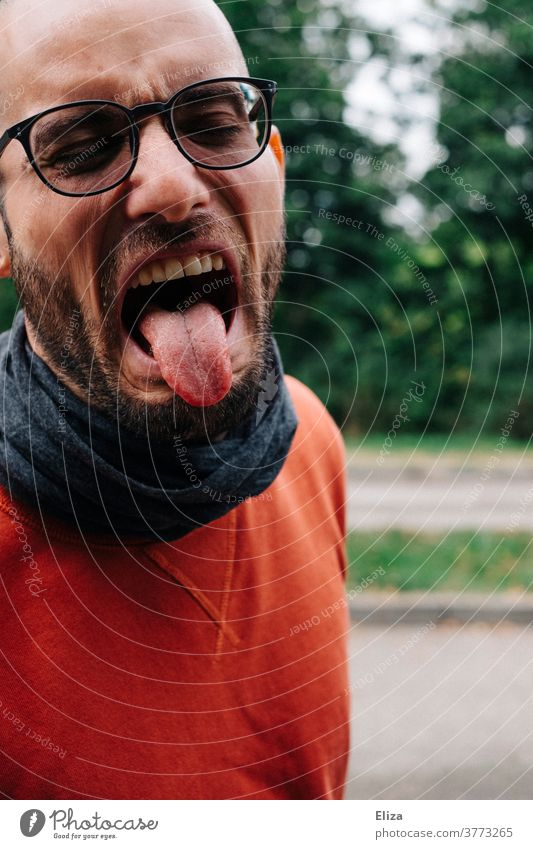 A man with glasses, beard and red sweater sticks out his tongue in disgust. Disgust stick out one's tongue disgusted bah Tongue Stick out Man Profile hate Yuck