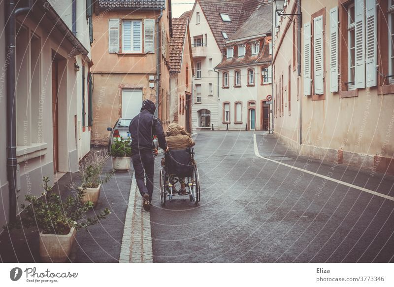 A man pushes a disabled person in a wheelchair down the street Wheelchair handicap Mobility Health care Rainy weather Illness Trip Push walking impediment
