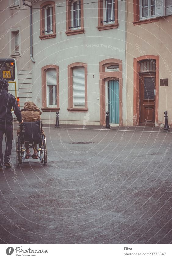 A man pushes a disabled person in a wheelchair Wheelchair handicap Mobility Health care Rainy weather Illness Trip Push walking impediment Handicapped Inclusion