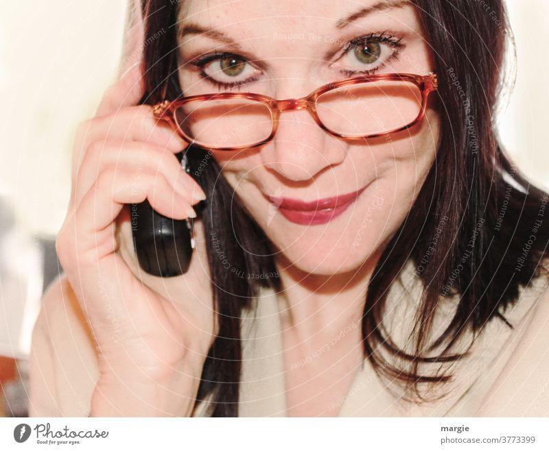 A woman looks over her glasses while talking on the phone Woman Eyeglasses Telephone Reading glasses eyes kind occupational Advertising Competent Career