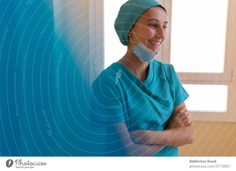 Cheerful nurse resting near window in hospital medic woman happy cheerful clinic work medical smile positive satisfied break young female professional delight