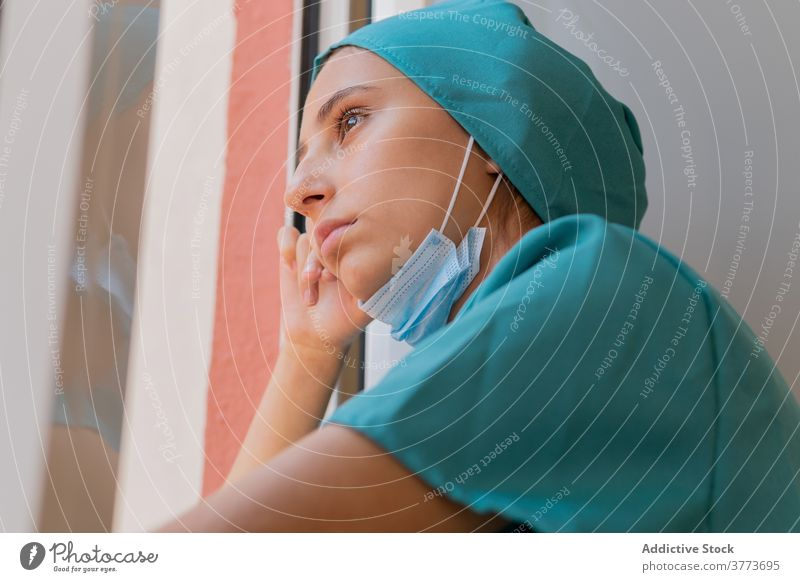 Pensive nurse looking at window medic pensive thoughtful tired woman hospital clinic break work contemplate dream think medical young female professional
