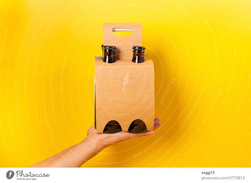 Hand holding a four pack beer presentation with yellow background ale bavarian belgian beverage booze bottle bottles box brand branding brewery carton case