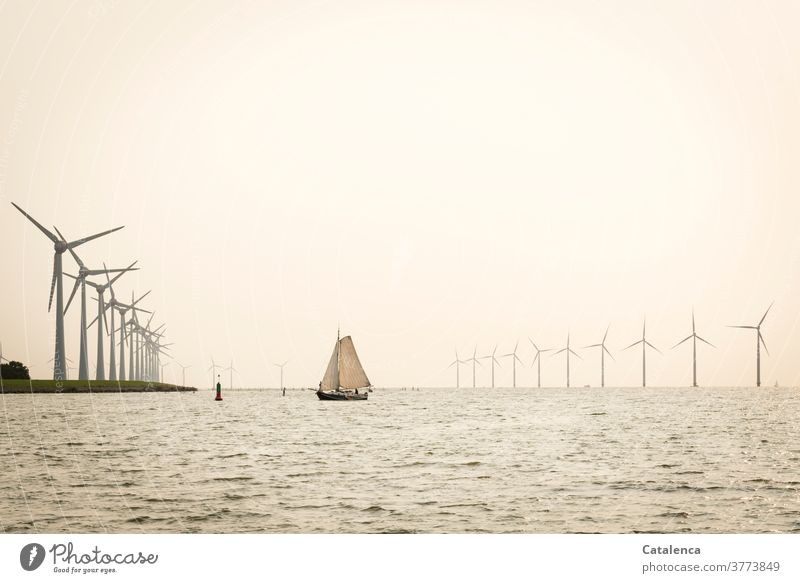A flat bottom ship in front of a wind farm in the IJsselmeer Renewable energy Energy windmills Nature Water Waves windy Navigation Ocean sailing yacht Horizon